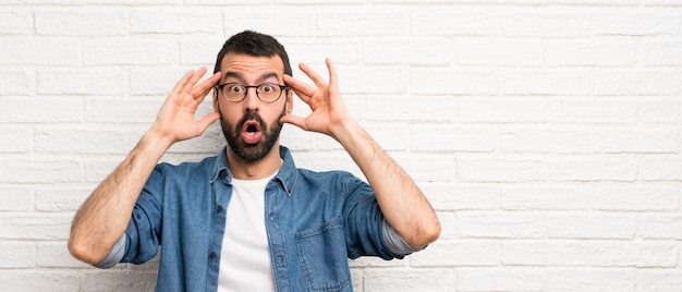 Handsome man with beard over white brick wall with surprise expression