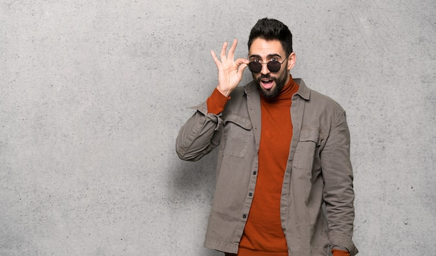 Handsome man with beard with glasses and surprised over textured wall