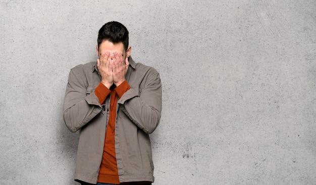 질감 벽에 피곤하고 아픈 표정으로 수염을 가진 잘 생긴 남자