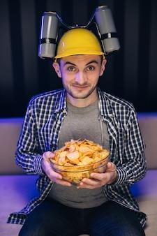 Красивый мужчина с пивным шлемом на голове смотрит телевизор и ест картофельные чипсы на диване у себя дома