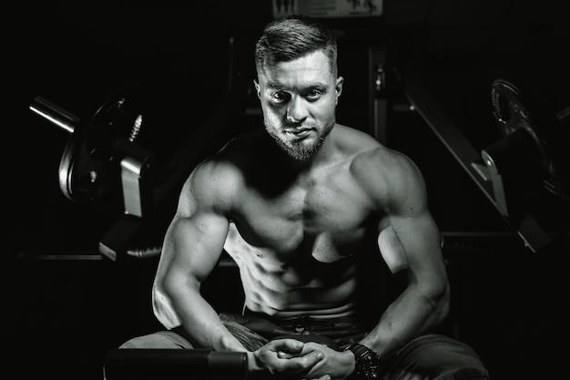 黒と青の背景、ジムのカメラでポーズをとって、大きな筋肉を持つハンサムな男。笑顔のボディービルダーの肖像画。閉じる。