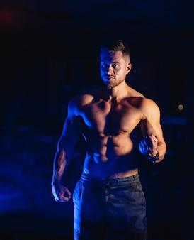 大きな筋肉を持つハンサムな男、ジムのカメラでポーズ、青い光。