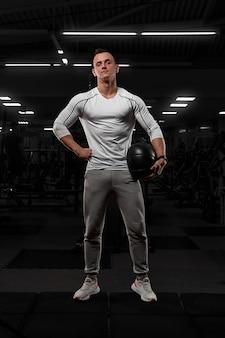 ジムのカメラでポーズをとって、大きな筋肉を持つハンサムな男。白いスポーツウェアのモデル