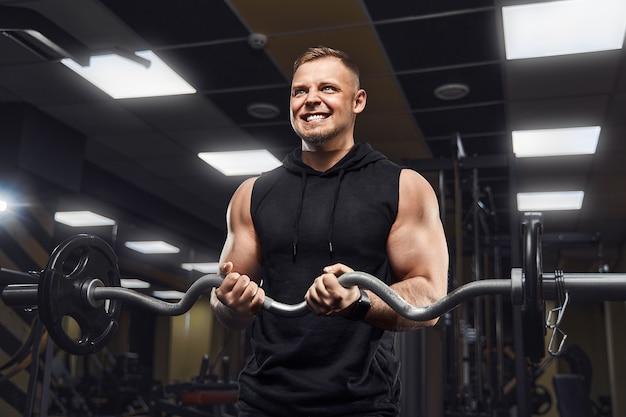 Красивый мужчина с большими мышцами позирует перед камерой в тренажерном зале