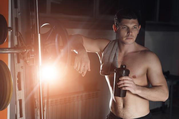 ジムのカメラでポーズをとって、大きな筋肉を持つハンサムな男。