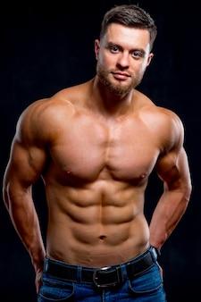 暗い背景のカメラでポーズをとって、大きな筋肉を持つハンサムな男。笑顔のボディービルダーの肖像画。閉じる。