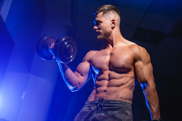Handsome man with big muscles, posing at the camera in the gym,