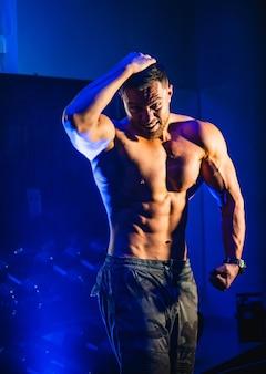 ジムでポーズをとって、大きな筋肉を持つハンサムな男
