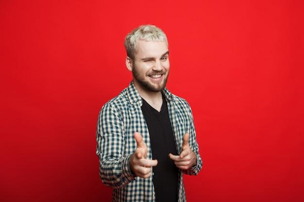 Красивый мужчина со светлыми волосами и бородой указывает на камеру, моргая