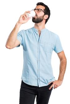 コーヒーを飲む青い眼鏡を持つハンサムな男