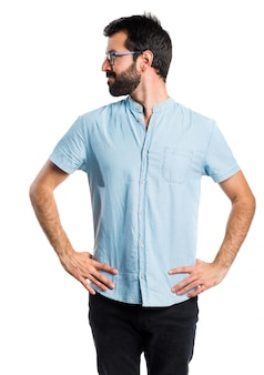 Uomo bello con gli occhiali blu che osservano lateralmente