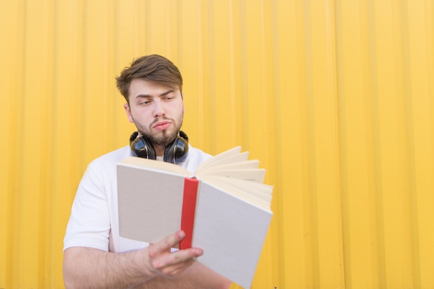 A handsome man with a book stands on a yellow wall and reads