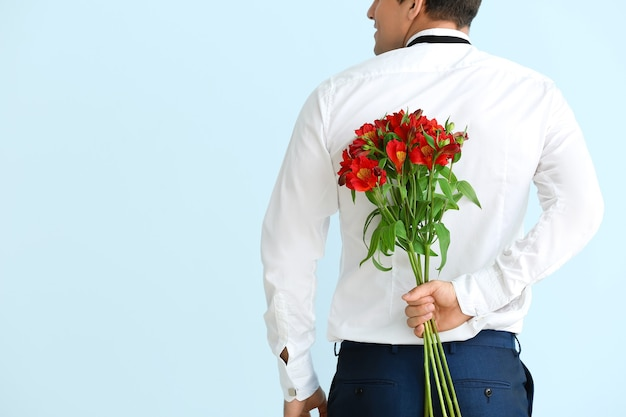 Handsome man with bouquet of flowers on color background