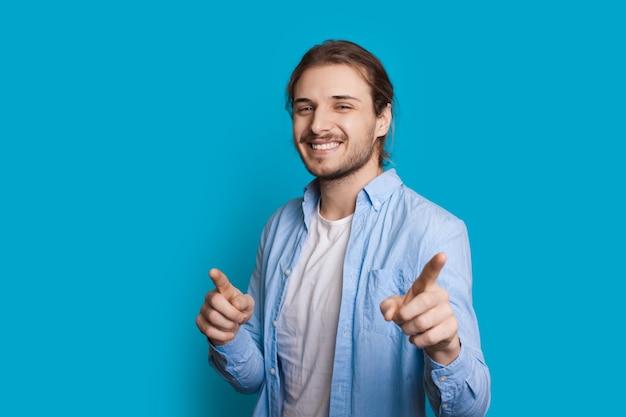 Красивый мужчина с щетиной и длинными волосами указывает на камеру, улыбаясь