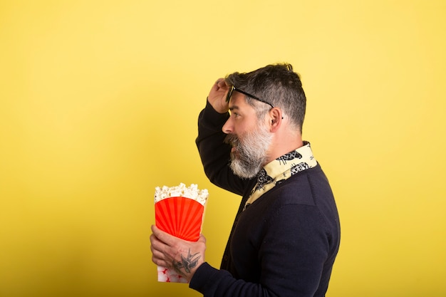 Handsome man with camera profile sunglasses holding a box full of popcorn on yellow background.