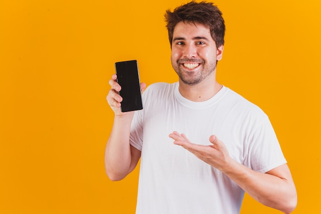 テキストのためのスペースを指して手に携帯電話を持つハンサムな男
