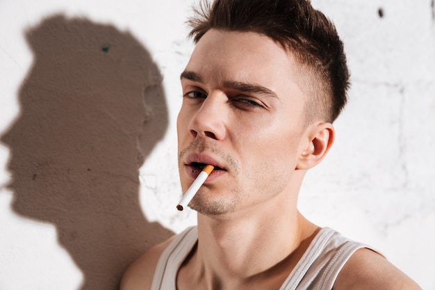 Красивый мужчина с сигаретой позирует на стене