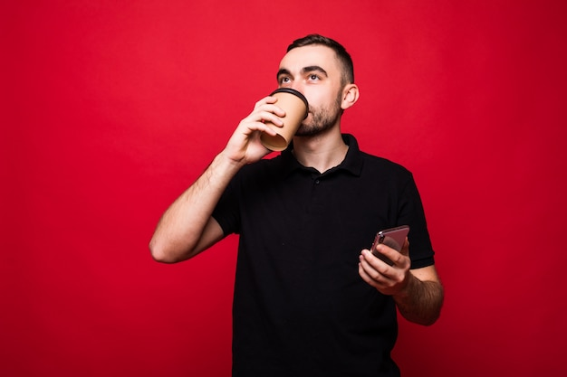 Handsome man with coffee cup to go read news on the phone isolated on red background