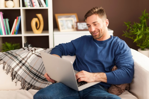 Красивый мужчина с современным ноутбуком дома