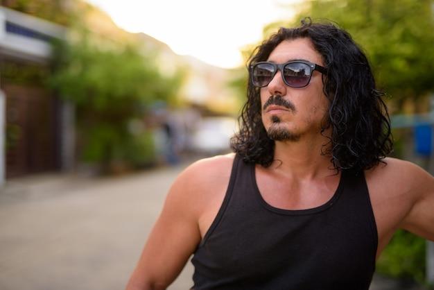 Красивый мужчина с вьющимися волосами и усами на улице на открытом воздухе