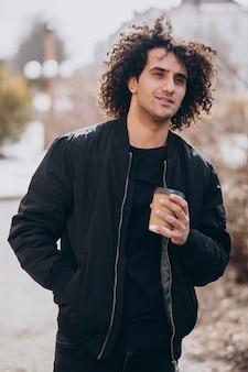 通りでコーヒーを飲みながら巻き毛のハンサムな男