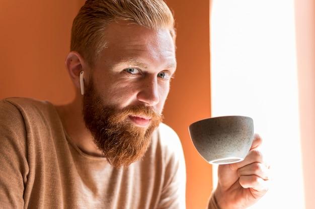 Uomo bello con gli auricolari che tiene una tazza di caffè