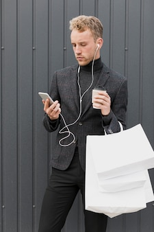 Handsome man with earphones near a gray wall