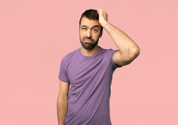 Handsome man with an expression of frustration and not understanding on isolated pink background