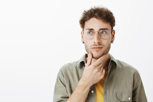 Красивый мужчина в очках позирует в студии