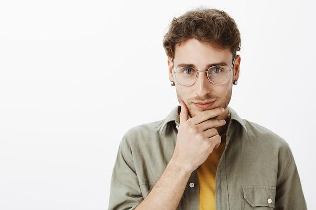 スタジオでポーズをとる眼鏡を持つハンサムな男