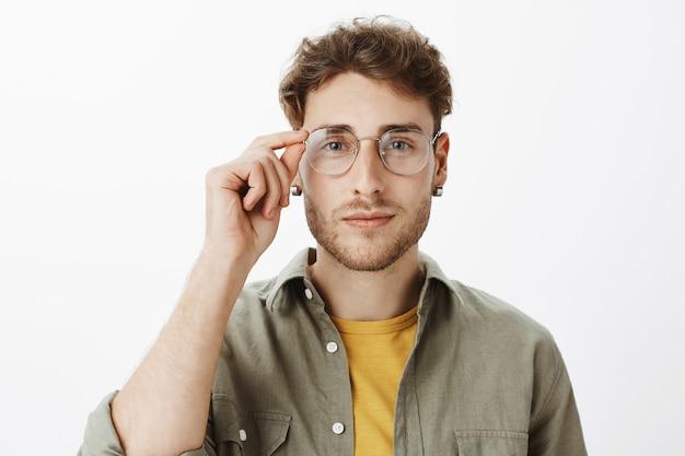 Uomo bello con gli occhiali in posa in studio