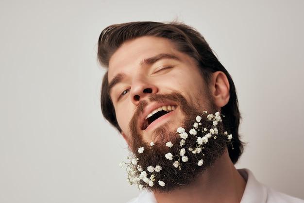 シャツのクローズアップでひげに花を持つハンサムな男