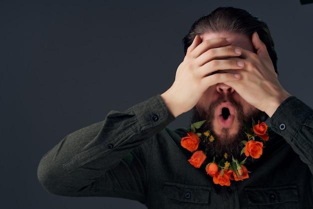 シャツの孤立した背景のひげに花を持つハンサムな男