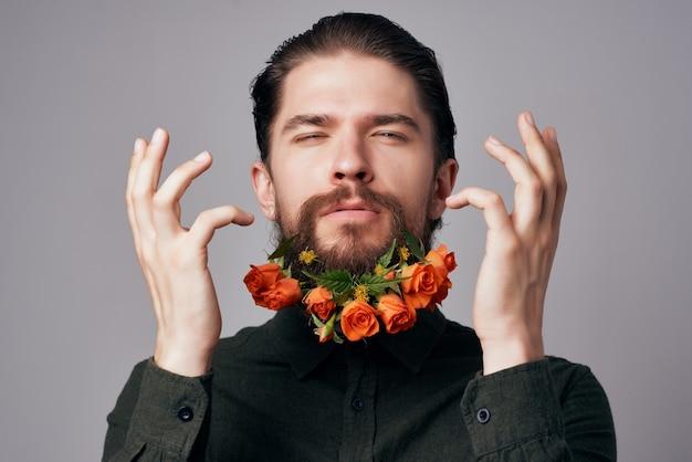 シャツスタジオのライフスタイルでひげに花を持つハンサムな男