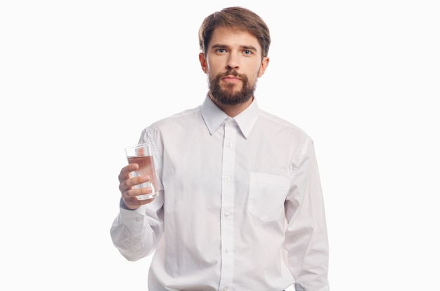 Красивый мужчина с стаканом воды здорового образа жизни белая рубашка светлая стена.