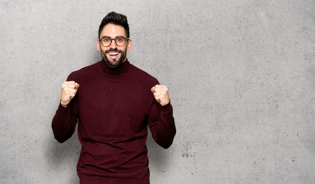 Handsome man with glasses celebrating a victory in winner position over textured wall