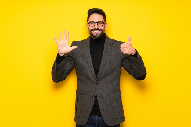 Handsome man with glasses counting six with fingers