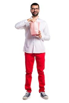 Uomo bello con bicchieri che mangiano popcorn