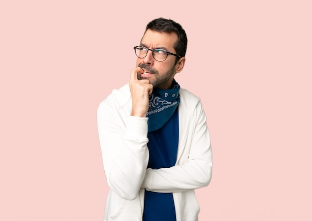 Handsome man with glasses having doubts while looking up on isolated pink background