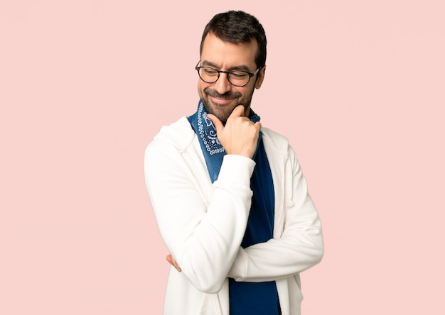 Handsome man with glasses looking down with the hand on the chin on isolated pink background