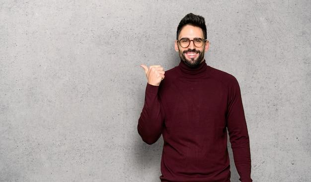 織り目加工の壁の上に製品を提示する側を指している眼鏡のハンサムな男