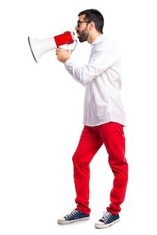 Handsome man with glasses shouting by megaphone