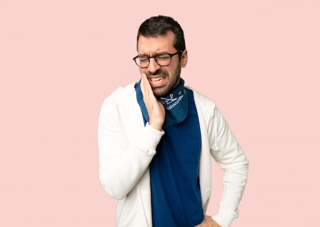 Handsome man with glasses with toothache on isolated pink background