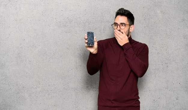 Handsome man with glasses with troubled holding broken smartphone over textured wall