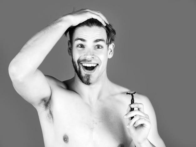半分剃った顔のあごとあごひげ、裸の胸で安全かみそりを保持している口ひげを持つハンサムな男。男性の美しさ、スキンケア、衛生。