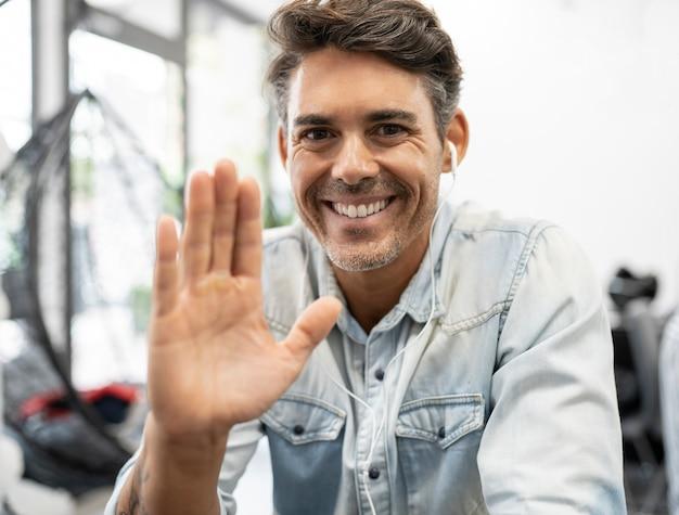 ヘッドフォンとコンピューターのビデオ通話を見て、彼の手で手を振るハンサムな男