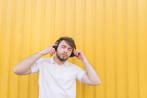 Handsome man with his eyes closed listening to music on wireless headphones on a yellow wall.