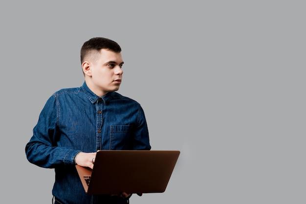 노트북과 잘 생긴 남자입니다. 집에서 온라인으로 작업하는 비즈니스 사람.