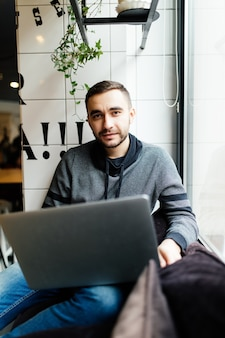 Красивый мужчина с ноутбуком в кафе