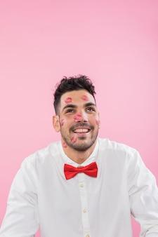 Красивый мужчина с помадой поцелуй отметки на лице